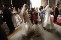 QUITO (14-09-07).- Blanca Socasi, una de las cincuenta novias, mientras Eva Aulestia, t'ía de su esposo, arregla su vestido, antes de la celebració—n del matrimonio masivo de polic'ías, en la Basí'lica del Voto Nacional, en Quito. Alfredo Cárdenas.