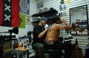 """Lima, Perú (Febrero de 2003).- Enrique Patiño, conocido como """"Kike"""", trabaja en la espalda de AndrŽés, miembro de la banda de rock Leucemia, en su local de tatuajes. Enrique tuvo que enfrentar la incomprensión de su familia, principalmente de su madre. Ella pensaba que se tatuaban solo los delincuentes y resentidos sociales, pero venció esa barrera y ahora tiene un negocio pr—óspero en el Centro Comercial Expocentro, en Lima - Perú. Alfredo Cá‡rdenas."""