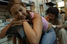"""Lima, Perú (Febrero de 2003).- Manolo trabaja tatuando un toro en el coxis de Karina Chacó—n, de 21 añ–os, en el local de tatuajes de su maestro Enrique Pati–ño, conocido como """"Kike"""", quien tuvo que enfrentar la incomprensión de su familia, principalmente de su madre. Ella pensaba que se tatuaban solo los delincuentes y resentidos sociales, pero venció esa barrera y ahora tiene un negocio próspero en el Centro Comercial Expocentro, en Lima - Perú. Alfredo C‡árdenas."""