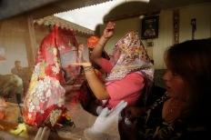 PILLARO, Tungurahua (01-01-2012).- Evelyn Constante (c) y Gabriela Alvarez (i), con la ayuda de Irma Carrillo (d) se visten de Parejas de L'nea, para participar en la tradicional fiesta de la Diablada de P'llaro, en la Comunidad de Tunguipamba, en el cant—n P'llaro, provicnia de Tungurahua. Alfredo Cardenas/ EL UNIVERSO